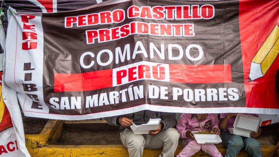 Seguidores de Castillo comen bajo una pancarta.