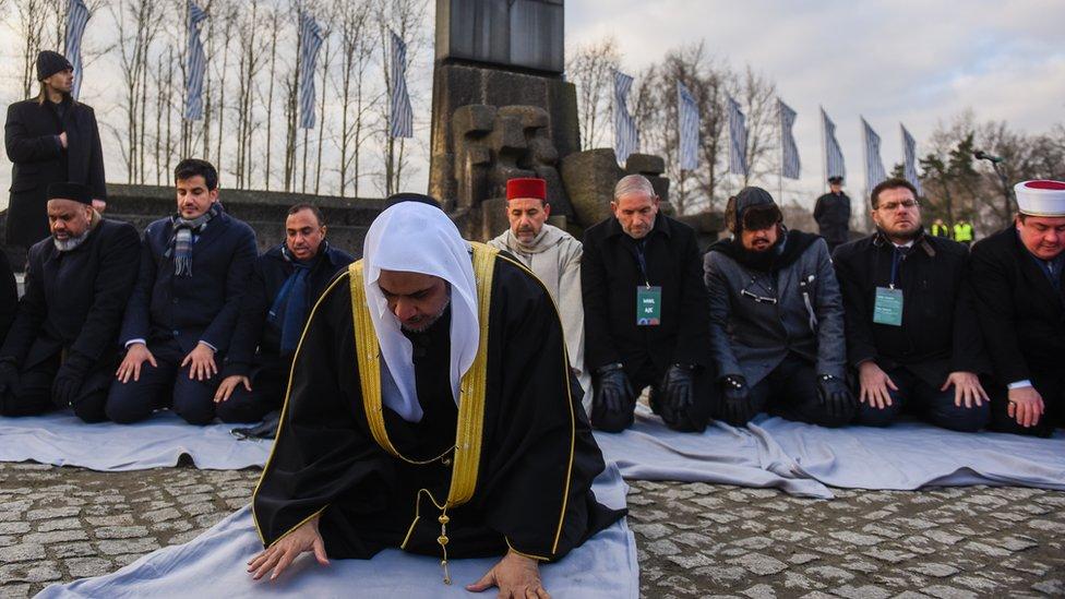 وفد من رابطة العالم الإسلامي يصلي في أحد معسكرات إبادة اليهود