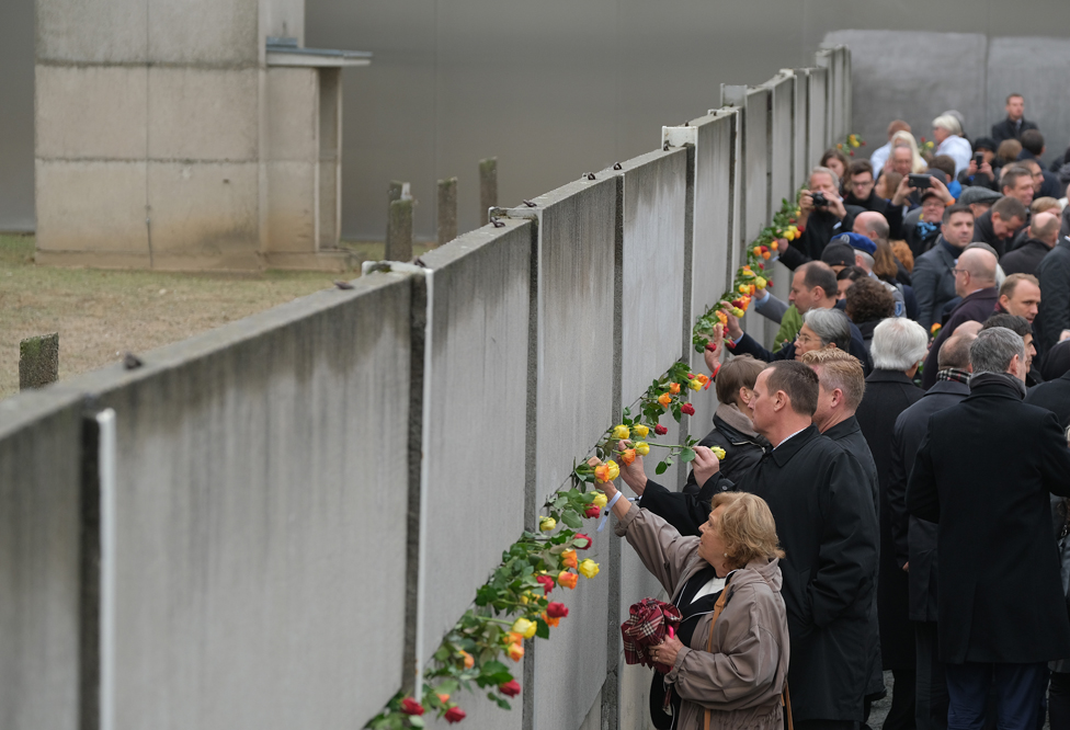 People stick flowers into slats of a still-standing section of the Berlin Wall, following a ceremony to celebrate the 30th anniversary of the fall of the wall in 1989.