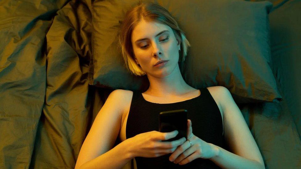 Chica con un teléfono en la mano en la cama.