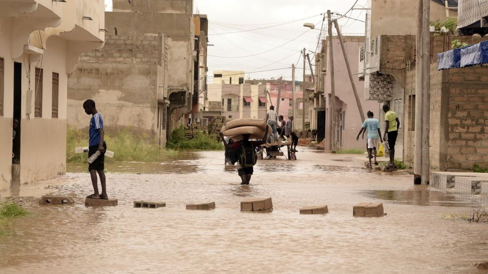 A man carries a mattress on his head while walking in flood water in the Keurs Massar area in Dakar on September 7, 2020 after heavy rains in Senegal.