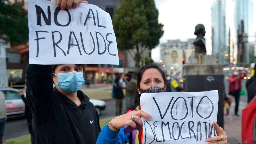 Dos seguidores de Yaku Pérez con carteles en contra del fraude.