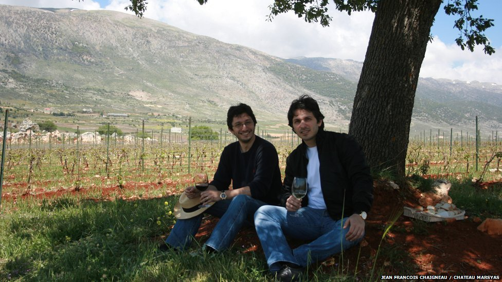 Karim and Sandro Saade enjoy a glass of wine in the shade of a tree