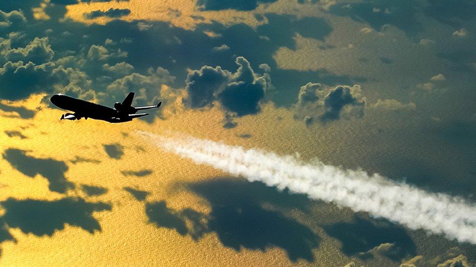 Avión de pasajeros en vuelo dejando una estela de humo
