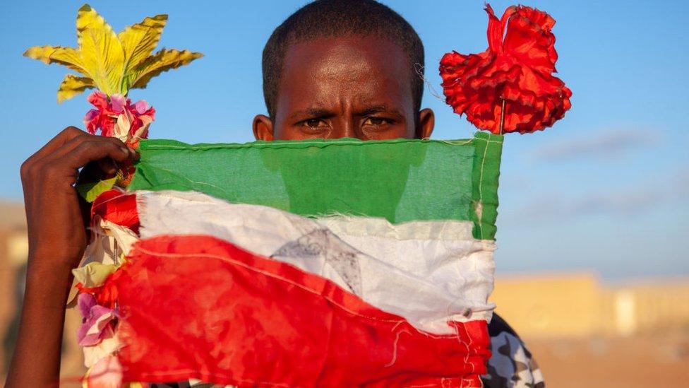 Un adolescente con una bandera nacional, región de Togdheer, Burao, Somalilandia