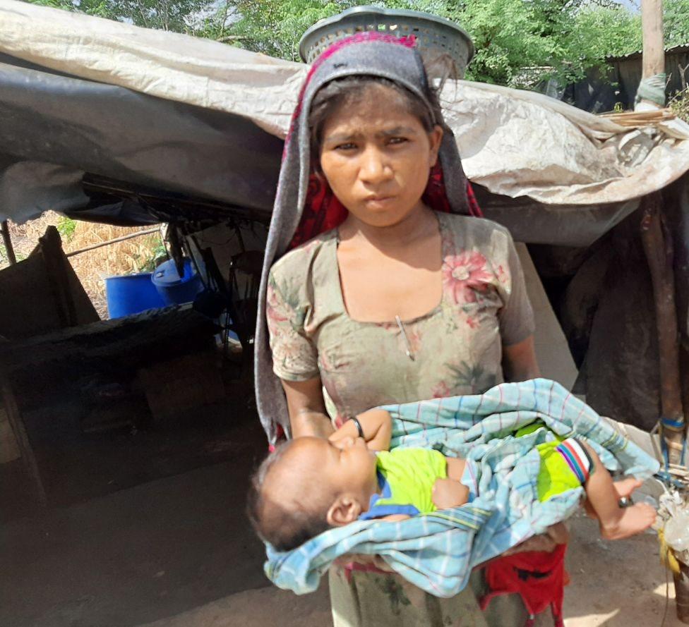 امرأة تحمل طفلا رضيعا