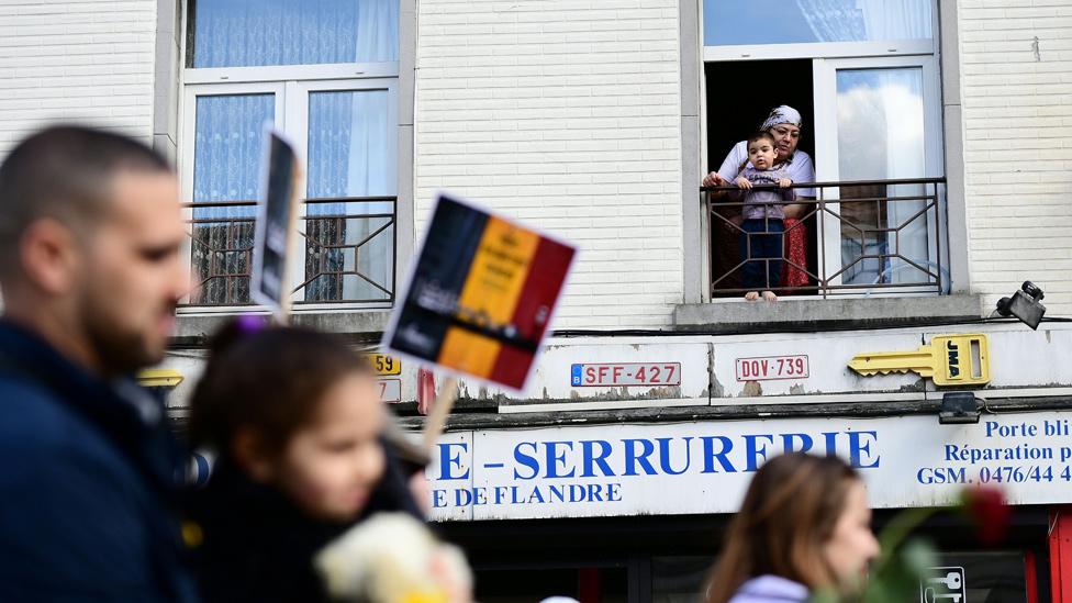 Madre musulmana con un niño mirando desde una ventana en Bélgica