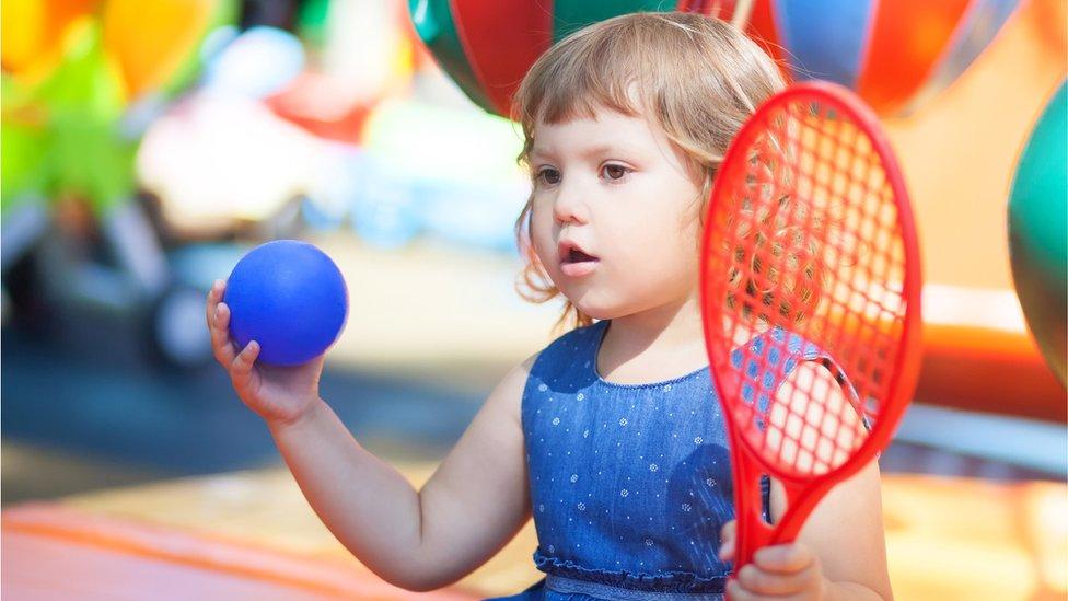 Niña de unos dos años con una raqueta y una pelota