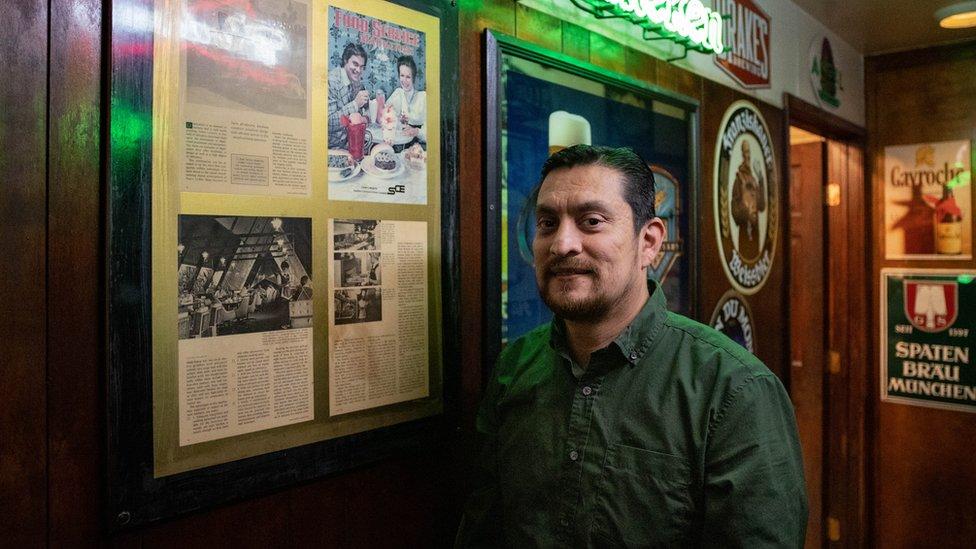 Sergio Vázquez posa al lado de recortes de un artículo sobre su bar cuando todavía era una cafetería en los años 70.