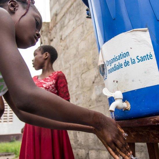 """Una niña se lava las manos con agua de un bote que dice """"Organizacón Mundial de la Salud""""."""