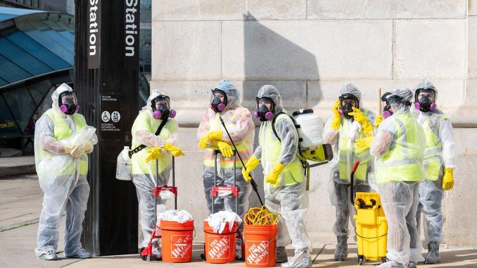 Cleaning workers in hazmat gear
