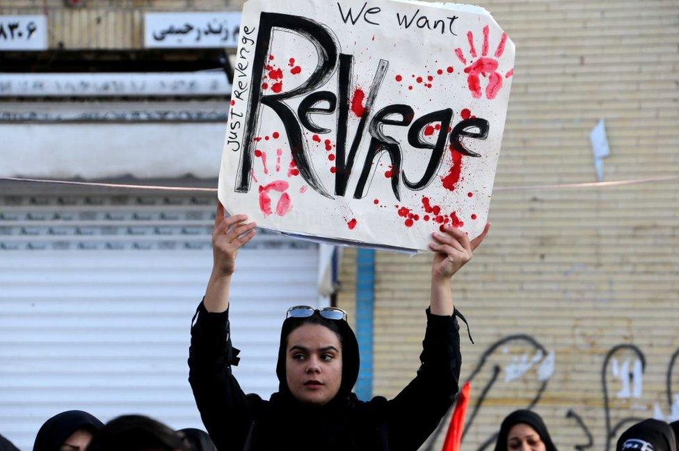 متظاهرة إيرانية ترفع لافتة تدعو إلى الثأر من الولايات المتحدة