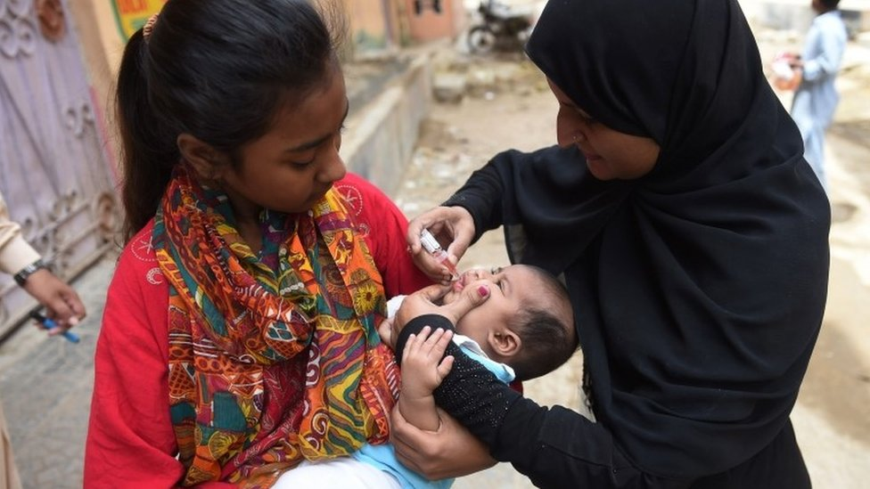 Pakistani health worker administers polio drops to a child in Karachi