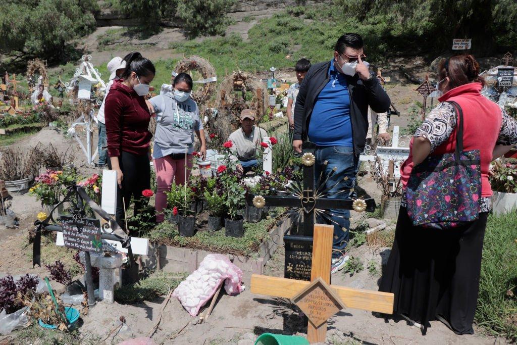 Parientes de personas fallecidas por covid-19 en un cementerio en México
