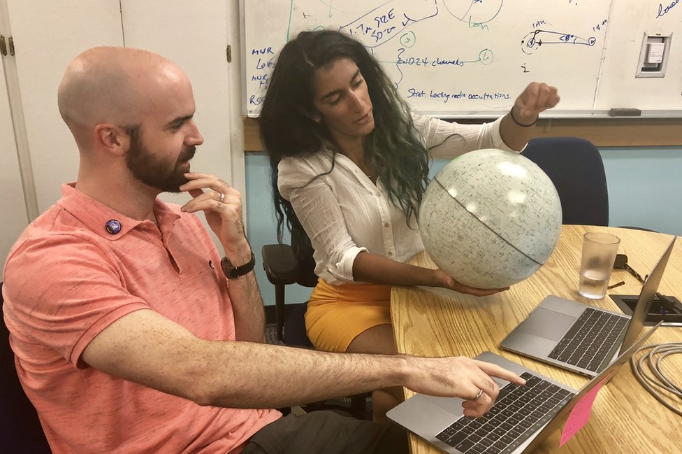 Two people look at a white globe of Mars. In the background there are whiteboards with calculations.
