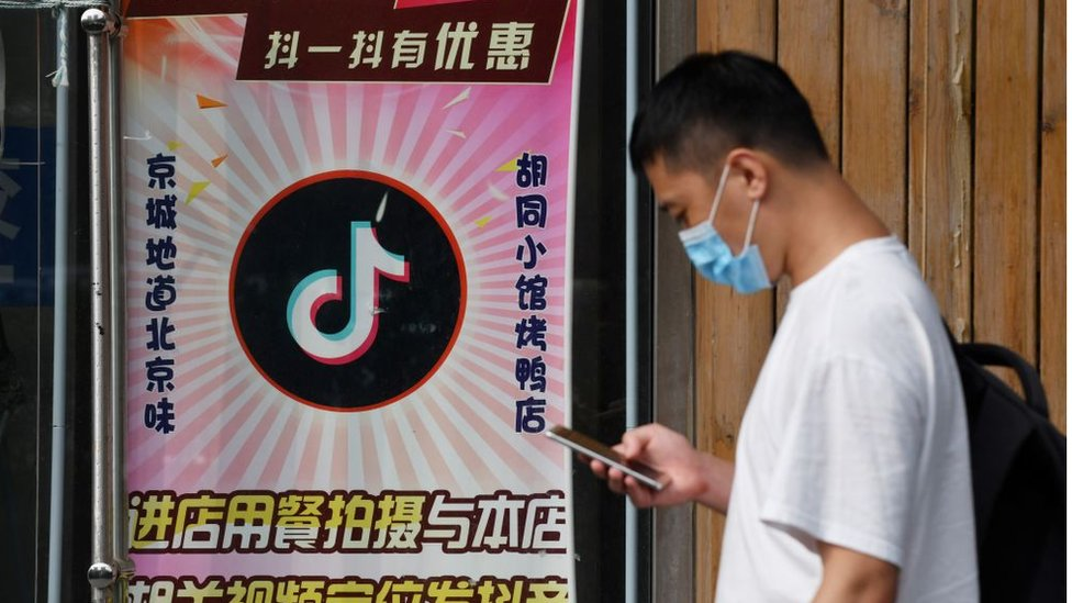 Un hombre pasa delante de un cartel con el logo de la compañía