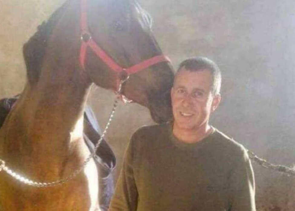 Khaled Mustafa smiling and standing with a horse.