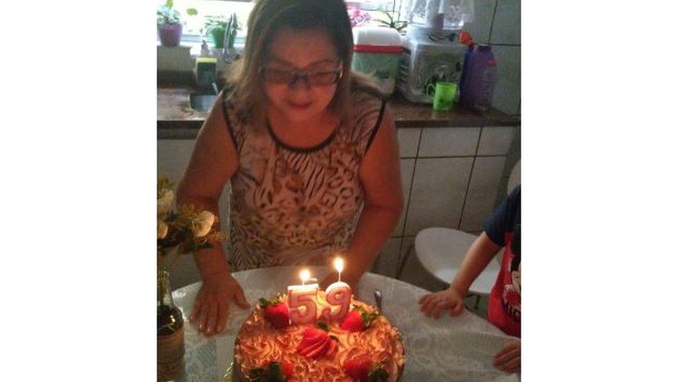 Ceci se prepara para assoprar a vela de seu bolo de aniversário de 59 anos