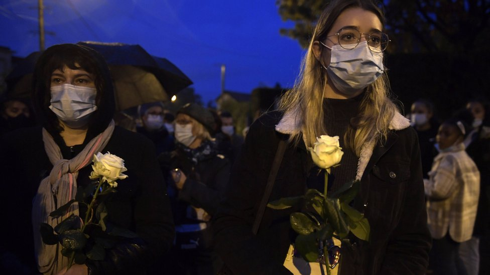 Two women march holding flowers