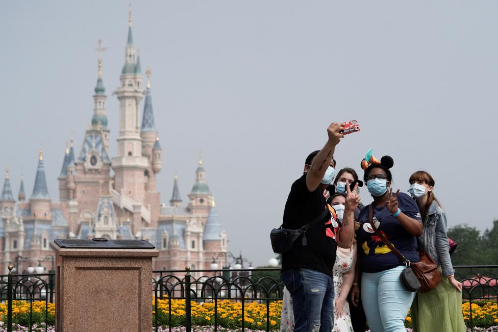Posetioci nose zaštitne maske i poziraju ispred ulaza u park