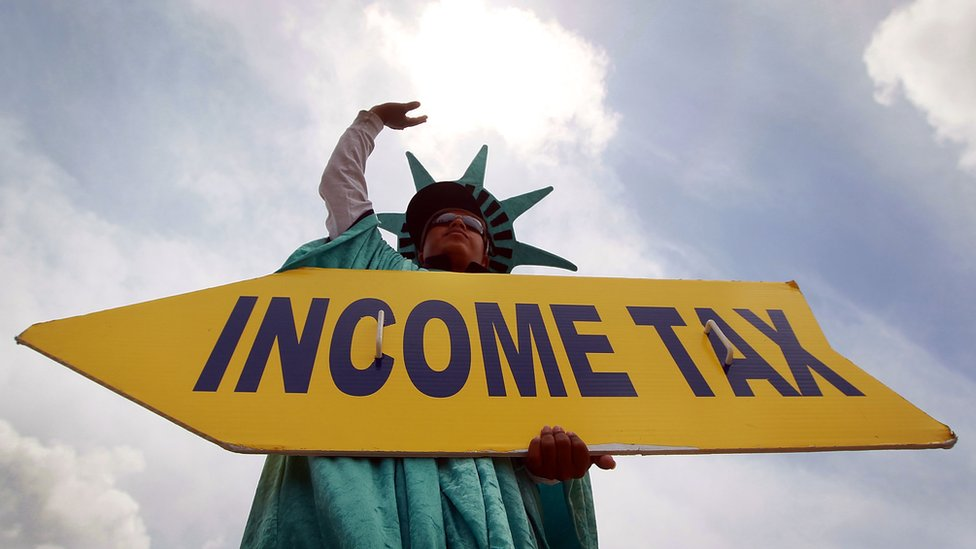 A man dressed at the Statue of Liberty holding a sign saying 'income tax'