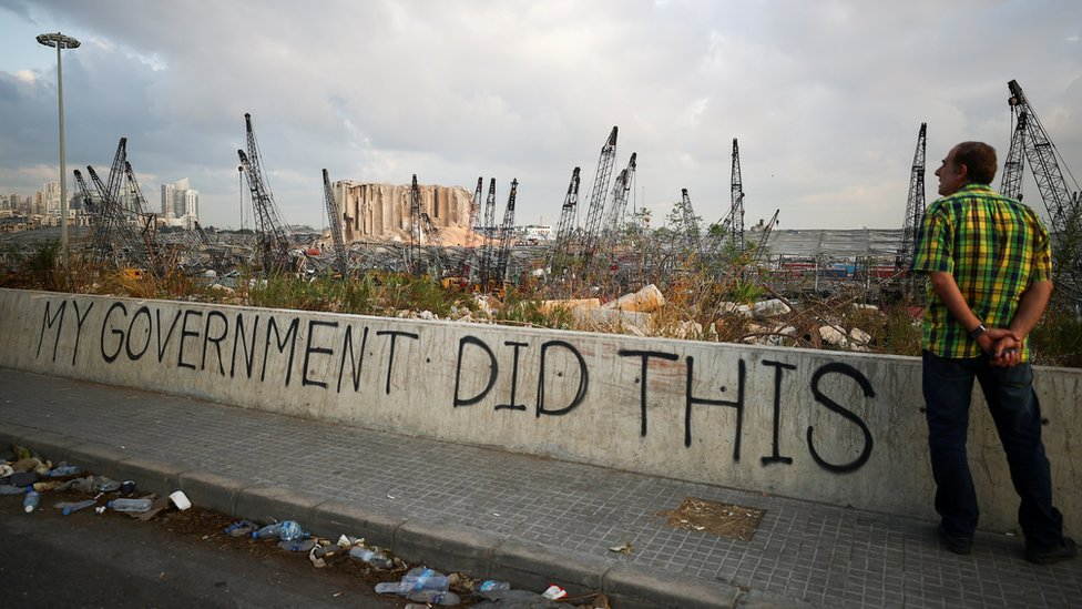 """A man stands next to graffiti saying """"my government did this"""", near Beirut's damaged port (11 August 2020)"""