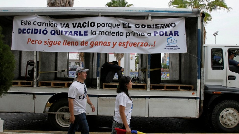 """People walk past a truck of Empresas Polar during a protest in Maracaibo, in the state of Zulia, Venezuela, April 29, 2016. The placard reads """"This truck is empty because the government decided to take the raw material to Polar. But still full of desire and effort!""""."""