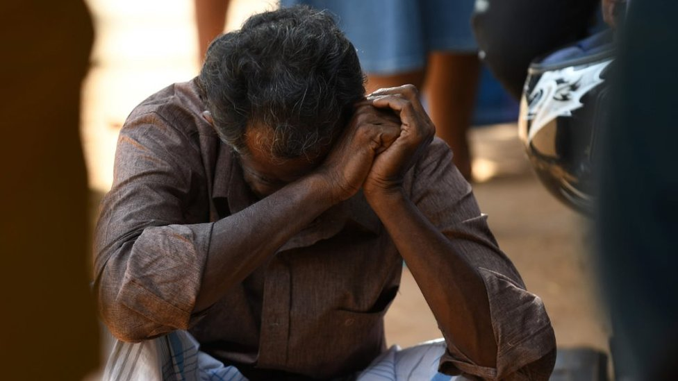 A man is hunched over outside a hospital in Batticaloa