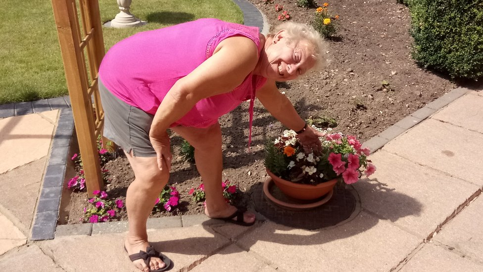 Lynn Wright in her garden next to a pot of flowers