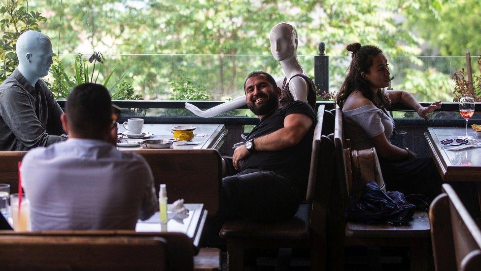 Em Istambul, um cliente posa para foto perto de manequins colocados em mesas de um café, de acordo com as regras de distanciamento social.