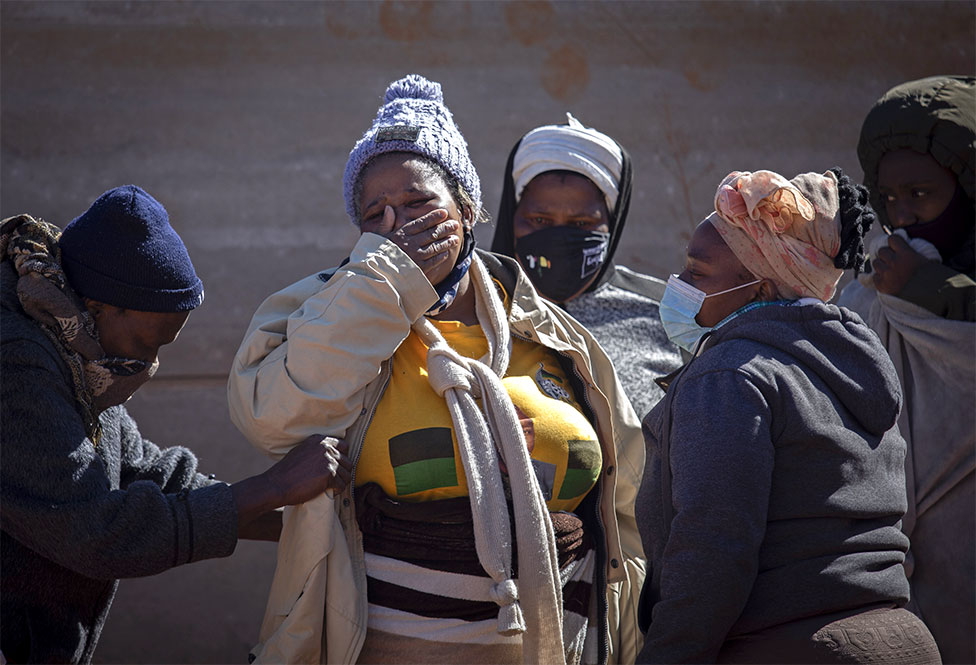 Familiares de un saqueador fallecido lloran junto a su cuerpo después de que saqueó bienes de las tiendas de la zona, Johannesburgo, Sudáfrica, el 13 de julio de 2021.
