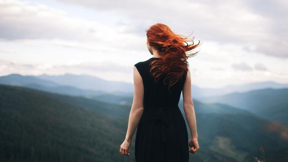 Mujer pelirroja mirando hacia el horizonte rodeada por montañas
