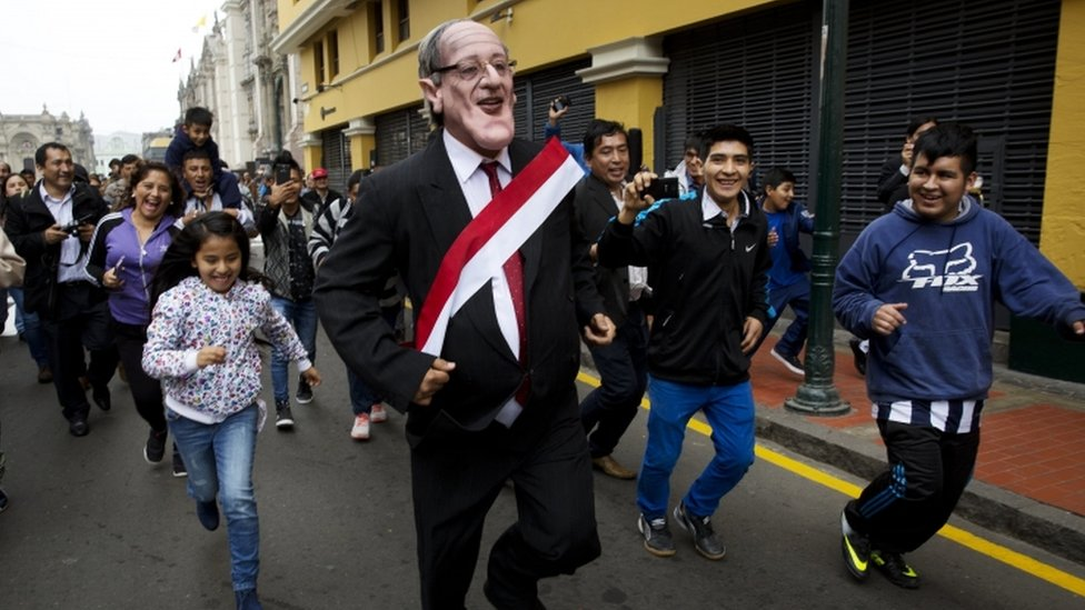 Children play with a man impersonating the new Peruvian president
