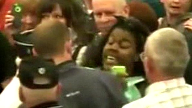 Woman (centre right) being jostled at Donald Trump rally