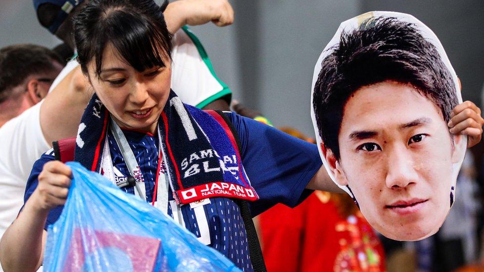 日本球迷在與塞內加爾2比2打平後整理看台。