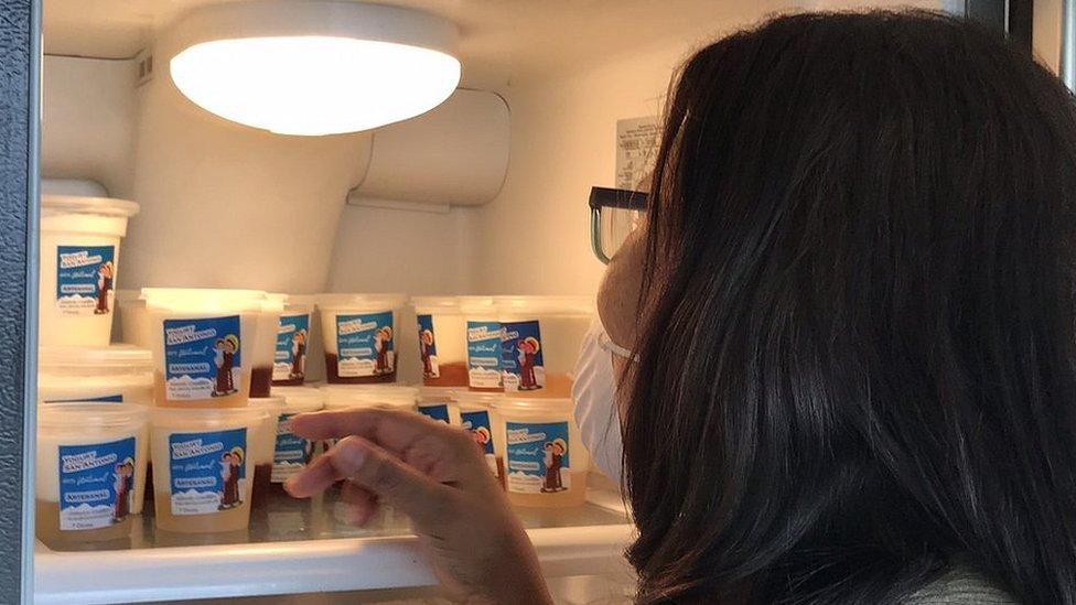 Una mujer frente a envases de yogurt en una refrigeradora.