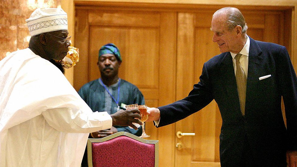 الرئيس النيجيري أولوسيجون أوباسانجو والأمير فيليب، دوق إدنبره ، أثناء حفل استقبال في أبوجا، نيجيريا، تكريما للملكة إليزابيث الثانية في دار الولاية في أبوجا 3 ديسمبر/كانون الثاني 2003 أثناء وصول الملكة إلى نيجيريا قبل يومين من قمة الكومنولث ، وكانت هي الزيارة الولى للمكاكة والدوق للبلاد بعد استقلالها عن بريطانيا في عام 1956.