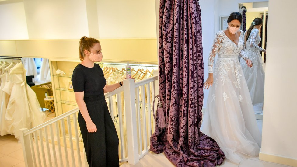 """Jessica Letheren exits the fitting room after changing into a wedding dress assisted by bridal consultant Felicity Gray at Allison Jayne Bridalwear in Clifton, Bristol, which has reopened following the lifting of coronavirus lockdown restrictions, with measures put in place to prevent the spread of coronavirus during brides"""" dress fittings"""