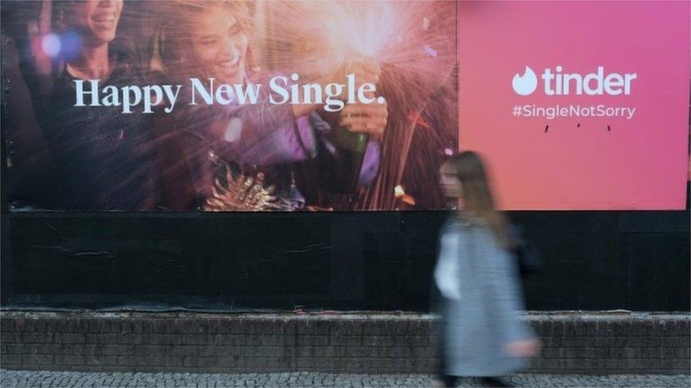 Mlada žena prolazi pored bilbord reklame za dejting aplikaciju Tinder