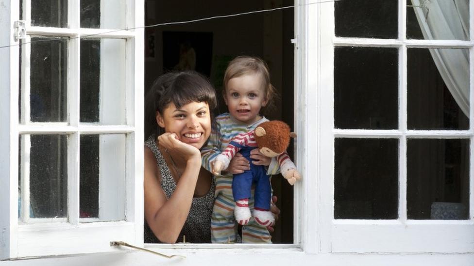 Mulher e bebê olhando de janela aberta