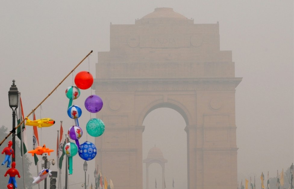 Inflatable toys are displayed for sale near the India Gate, seen engulfed in smog in Delhi on 5 November,2016.