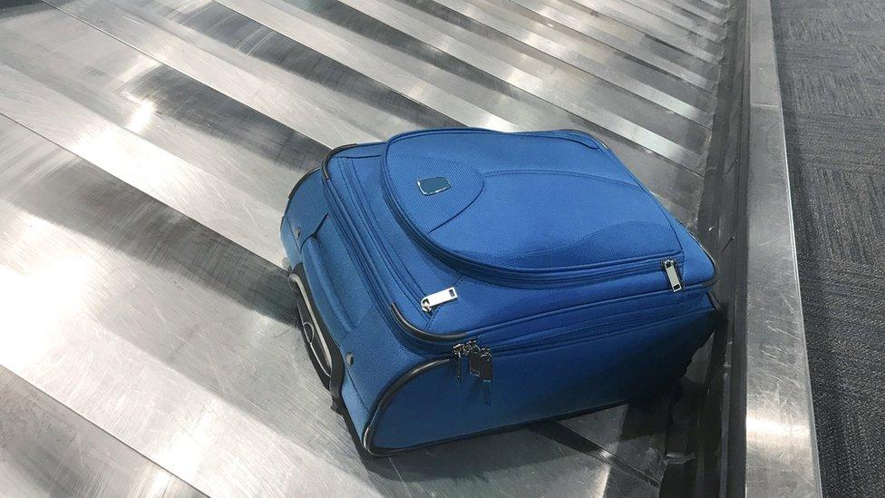 maleta azul en una cinta de equipajes de aeropuerto.