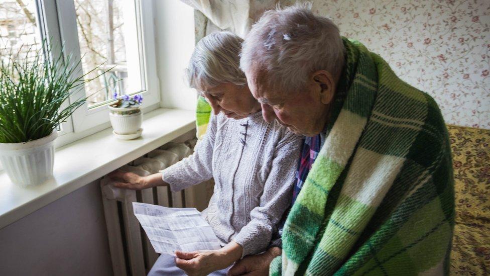 Elderly couple look at heating bill
