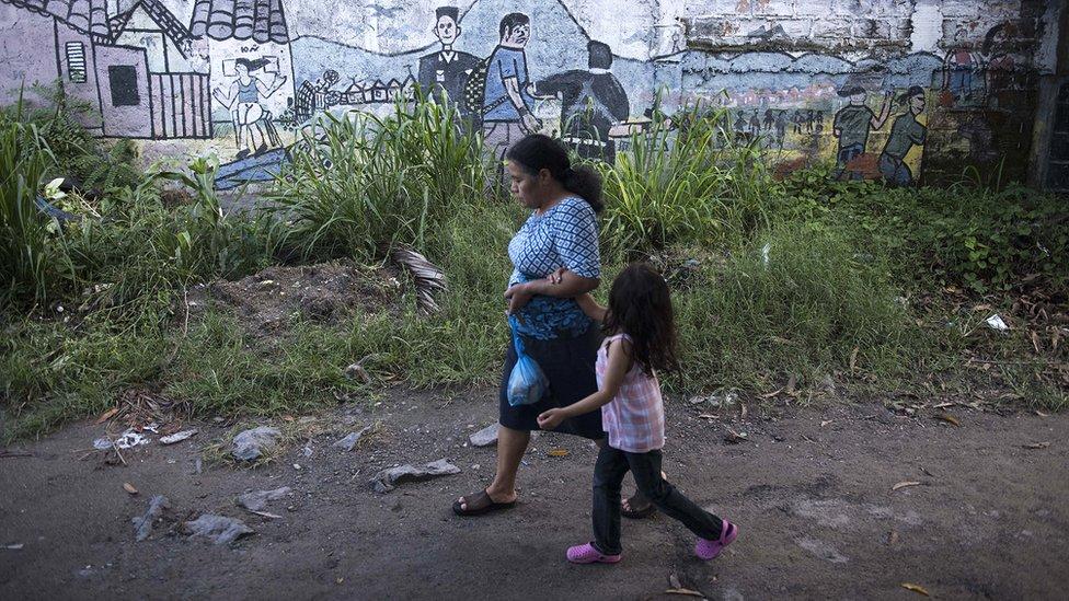 BBC, NO USAR | Mujer mayor pasea con una niña en un barrio de San Salvador.
