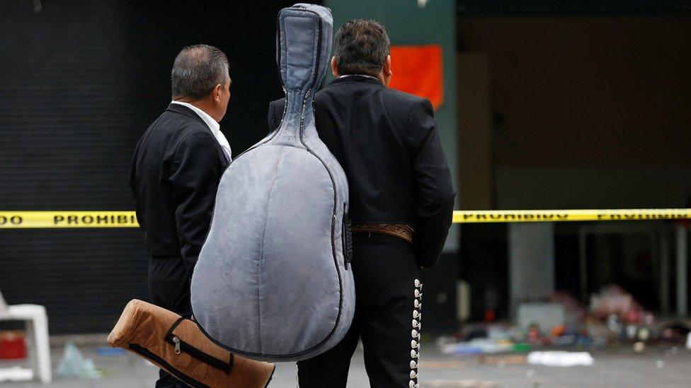 Dos mariachis miran la escena del crimen