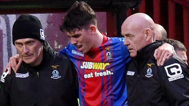 Inverness midfielder Ryan Christie is helped off the field following injury