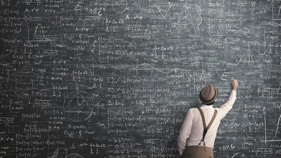 hombre escribiendo fórmulas en una pizarra