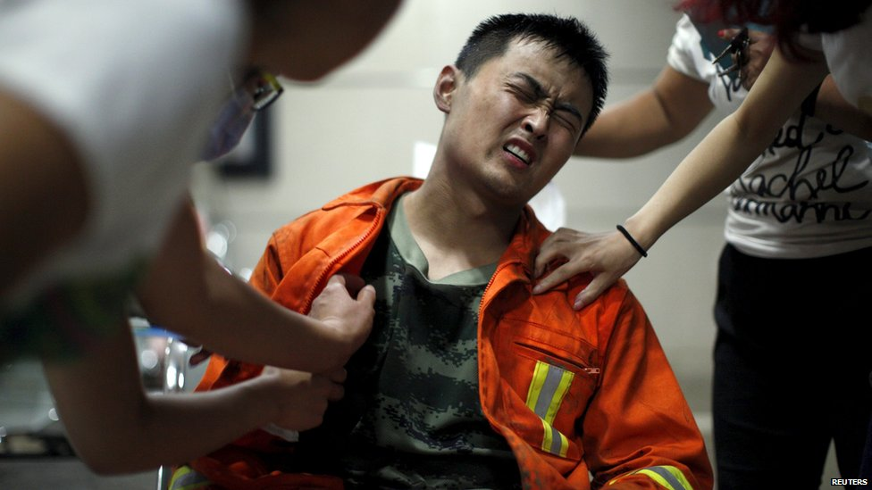 A firefighter reacts as he receives treatment at a hospital after the explosions at the Binhai new district in Tianjin, China, August 13, 2015.