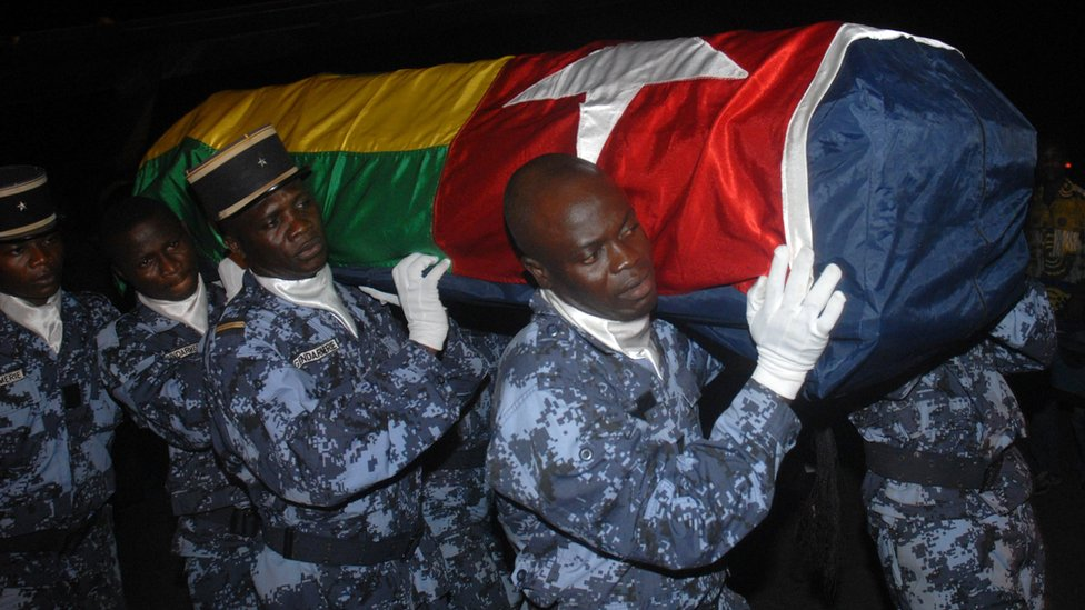 Togolese gendarmes carry the coffin wrapped in the national flag of one of the victims of the rebel attack that killed two of members of the Togolese national football team on 9 January 2010 after the team's arrival at Lome airport on 11 January 2010.
