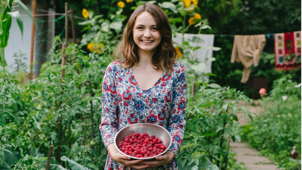 Mujer con frutas del bosque en un jardín.